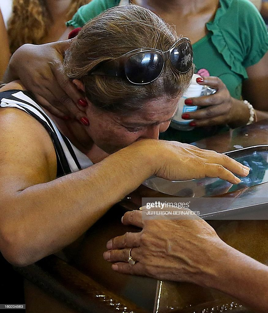 Relatives of victims from a fire that broke out at a nightclub weep during their funeral in Santa Maria, 550 Km from Porto Alegre, southern Brazil on January 27, 2013. At least 232 people died and 131 were injured early Sunday when a fire tore through a nightclub packed with university students in the southern Brazilian city of Santa Maria, police said. AFP PHOTO / Jefferson BERNARDES