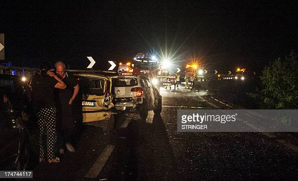 Relatives of victims of a bus crash stand among damaged cars on July 28 2013 on the road between Monteforte Irpino and Baiano southern Italy At least...
