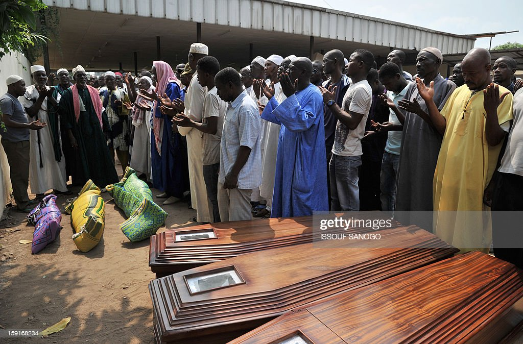 Relatives of victims of a stampede pray next to coffins in front of the Treichville morgue in Abidjan, on January 9, 2013. The official death toll rose to 63 two days after a New Year stampede, which broke out among crowds returning from a fireworks display in the economic capital Abidjan. AFP PHOTO / ISSOUF SANOGO