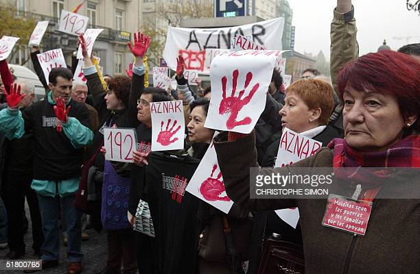 Relatives of victims of the 11 March Madrid bomb attacks protest with hands painted red signifying former Prime Minister Jose Maria Aznar's guilt at...