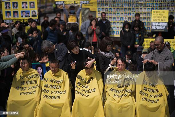 Relatives of victims of the Sewol ferry accident have their heads shaved during a protest ahead of the anniversary of the disaster in Seoul on April...