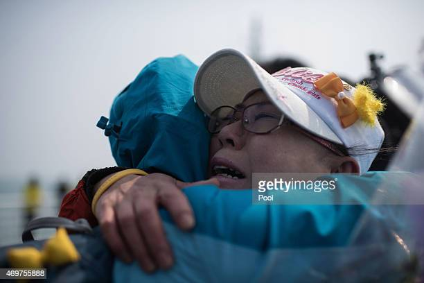 Relatives of victims of the Sewol ferry disaster weep as they stand on the deck of a boat during a visit to the site of the sunken ferry on April 15...