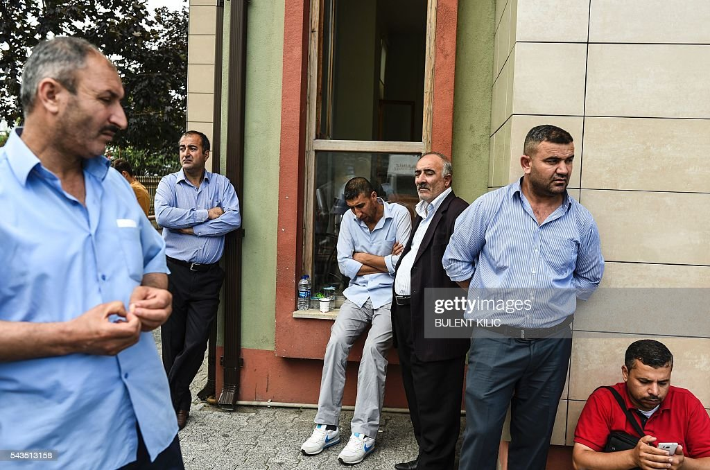 Relatives of victims wait outside a forensic medicine building close to Istanbul's airport on June 29, 2016, a day after a suicide bombing and gun attack targetted Istanbul's airport. A triple suicide bombing and gun attack that occurred on June 28, 2016 at Istanbul's Ataturk airport has killed at least 36 people, including foreigners, with Turkey's prime minister saying early signs pointed to an assault by the Islamic State group. / AFP / BULENT