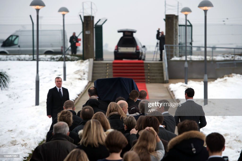 Relatives of Yann Desjeux, 53, French citizen who was killed in the hostage rescue operation at a remote gas plant seized by Islamist militants in Algeria, follow the coffin at the Roissy airport, outside Paris, on January 24, 2013 in Roissy-en-France.