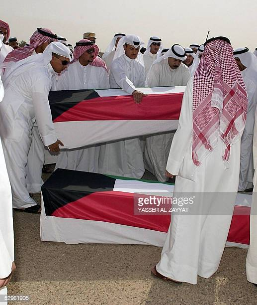 Relatives prepare to bury the remains of four Kuwaitis found recently in a mass grave in Iraq 21 May 2005 at a cemetery in Kuwait City The remains of...