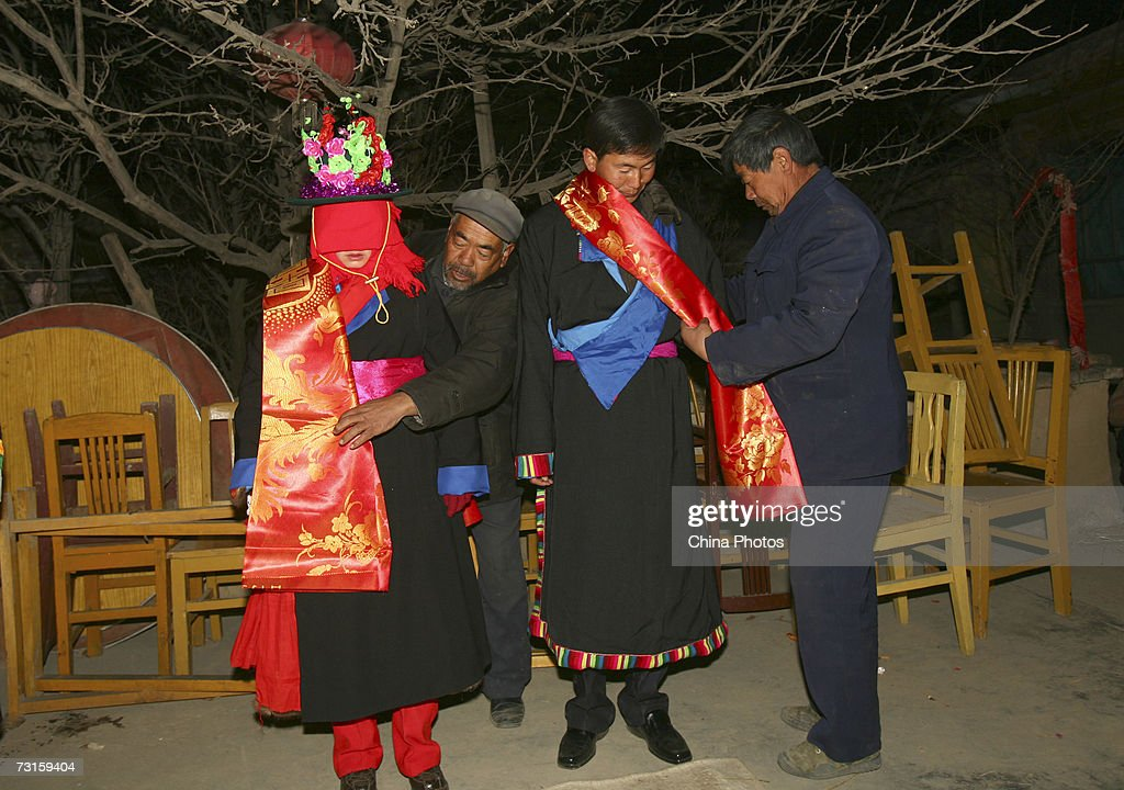 Relatives put red silk on the groom Qi Xinghe and bride Luo Jinhua during a Tu ethnic minority group wedding ceremony on January 30, 2007 in Huzhu County of Qinghai Province, northwest of China. The wedding lasts two days. During the first day of the ceremony, relatives of the groom bring gifts to the bride's home. The brides relatives then shut the door and sing to test the sincerity of the groom. The Bride's family finally welcome in the guests and they dance to celebrate the marriage. During the early morning of the second day, the families help the bride dress up and the girl bids thanks and farewell to her parents. At dawn, the groom rides a horse to pick up the bride and the short ceremony is held at the groom's home. Relatives of both families then enjoy a grand feast. The newlyweds bid farewell to the relatives of the bride at dusk as the ceremony ends.