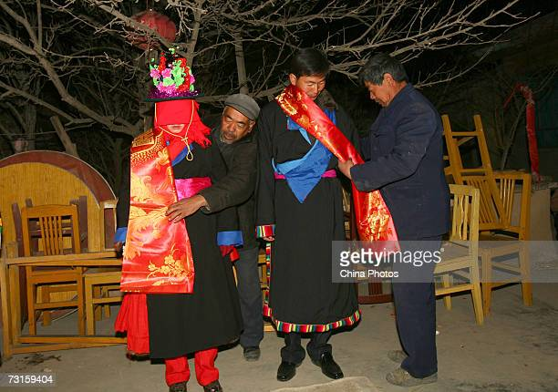 Relatives put red silk on the groom Qi Xinghe and bride Luo Jinhua during a Tu ethnic minority group wedding ceremony on January 30 2007 in Huzhu...