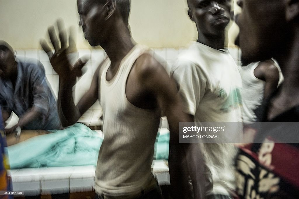 Relatives react as two bodies are prepared in the morgue of the General Hospital in Bangui on May 28 2014 after ten people were killed and several...