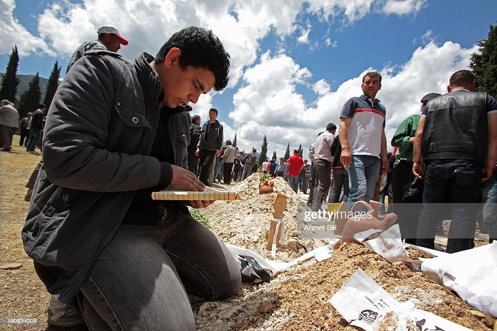 Relatives read the holy Kur'an during a funeral for the victims of a mining disaster on May 15 2014 in Soma a district in Turkey's western province...