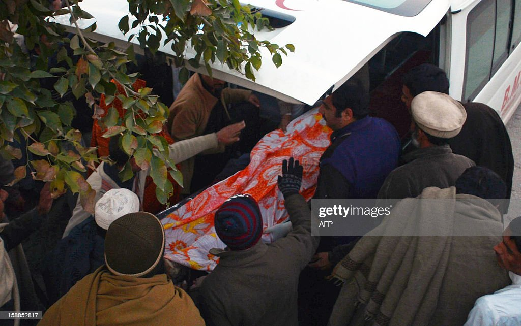 Relatives shift the body of a charity worker into an ambulance following an attack by gunmen in Swabi on January 1, 2013. Six women and a man working for a Pakistani health and education charity involved in vaccinations were shot dead on their way home from a community centre, officials said.