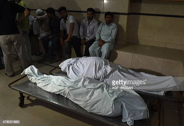 Relatives sit next to the dead bodies of heatwave victims at the cold storage of the EDHI center in Karachi on June 21 2015 A heatwave has killed at...