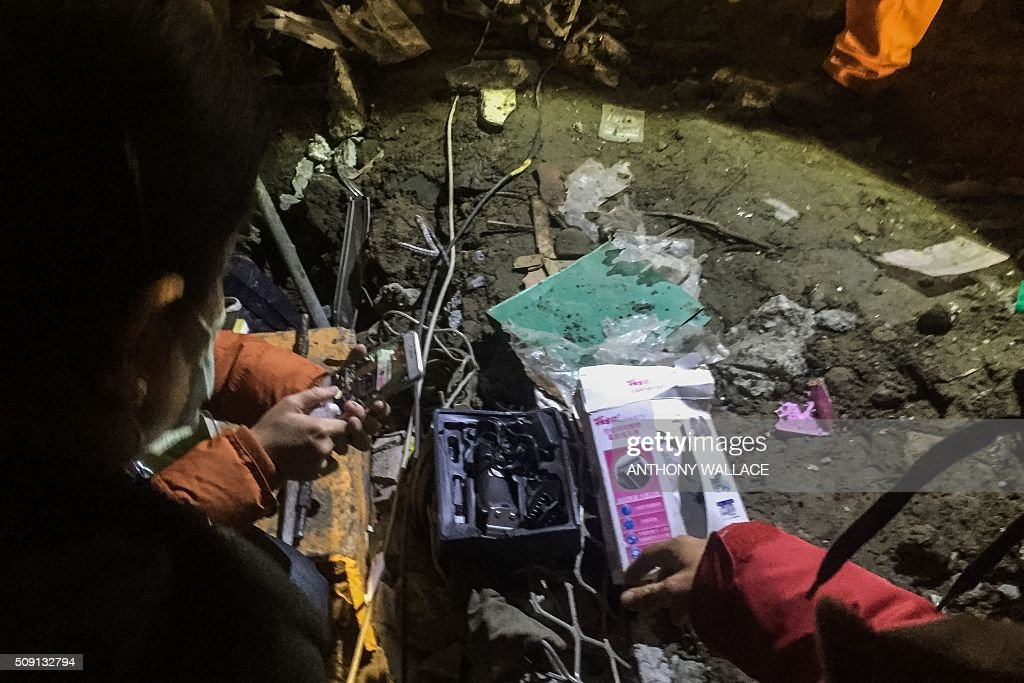 Relatives take a photo of hair clippers retrieved from rubbles by rescue workers which might belong to their trapped loved ones, from the remains of a building which collapsed in the 6.4 magnitude earthquake, in the southern Taiwanese city of Tainan early on February 9, 2016. Rescuers deployed heavy machinery on February 9 in a renewed effort to locate more than 100 people trapped in the rubble of a Taiwan apartment complex felled by an earthquake as the 72-hour 'golden window' for finding survivors passed. AFP PHOTO / ANTHONY WALLACE / AFP / ANTHONY WALLACE
