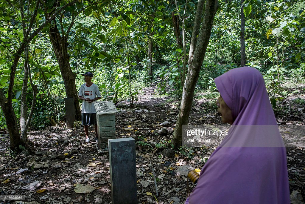 Relatives visit the site that is believed to be the burial ground for victims of Indonesia's anti-communist massacre, inside the teak forest in Plumbon village on May 03, 2016 in Semarang, Central Java, Indonesia. Survivors of Indonesia's anti-communist massacres called for investigations into the country's purges, in which possibly half a million to one million people died beginning October 1965, during the crackdown by the Indonesian government and military after an attempted coup by suspected communists.