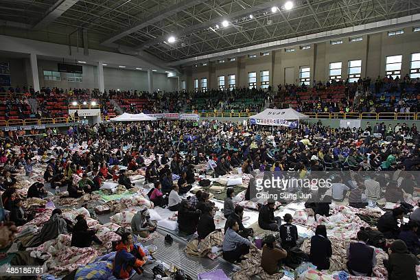 Relatives wait for missing passengers of a sunken ferry at Jindo gymnasium on April 17 2014 in Jindogun South Korea Six are dead and 290 are missing...