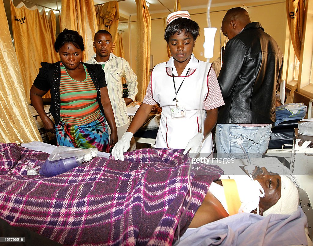 Relatives watch as a nurse attends to one of the survivors, Costantino Labulayi ,34, at the University Teaching Hospital (UTH) in Lusaka following an accident that killed 17 passengers and left four survivors after a Lusaka bound passenger service mini bus collided with an oncoming truck after one of the tyres burst in Chisamba on April 30, 2013. APF