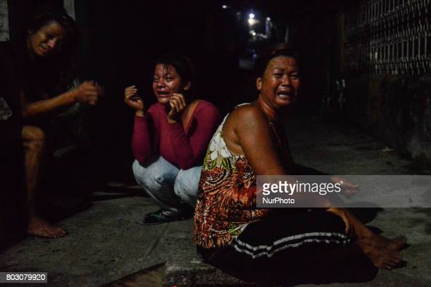 Relatives weep near the scene where a man was shot dead by police following a police operation against illegal drugs in Caloocan north of Manila...