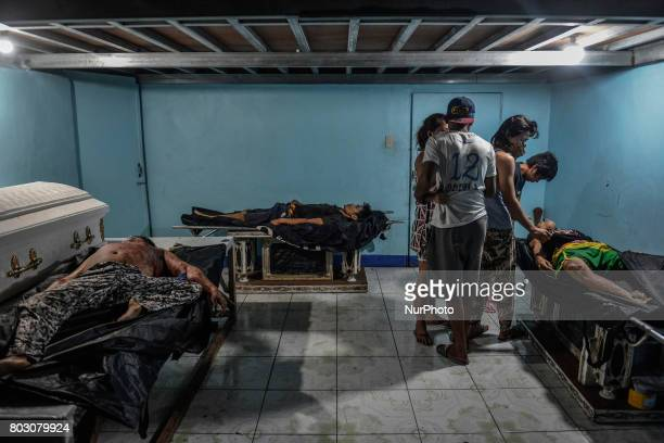 Relatives weep over the body of Julius Soriano who was shot dead by police following a police operation against illegal drugs as other bodies lie...