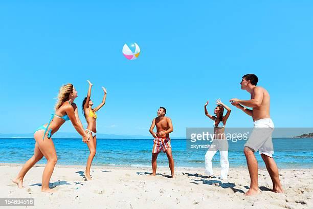 Activité de détente sur la plage, les personnes jouant de volley-ball.