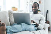 Handsome young African man looking at laptop and smiling while lying on the sofa at home