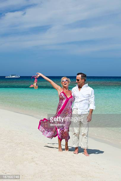 Relaxed adult couple walking along tropical beach