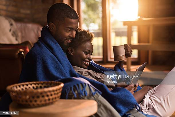 Relaxed African American couple using digital tablet at home.