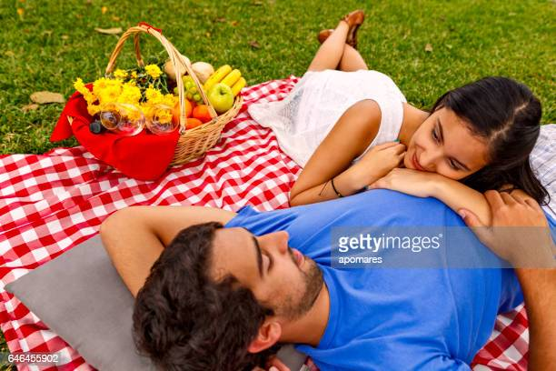 Relaxed and loving Latin happy couple enjoying picnic in park