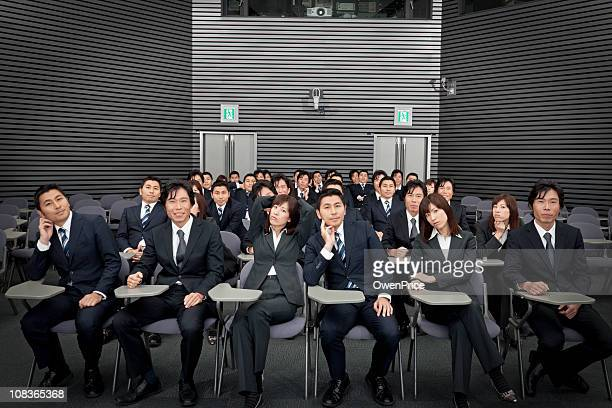 Relaxed business people in lecture theatre