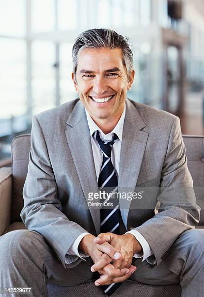 Relaxed businessman in modern interior, smiling