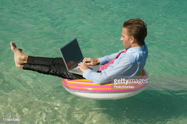 Relaxed Businessman Keeping Afloat on Tropical Sea with Laptop