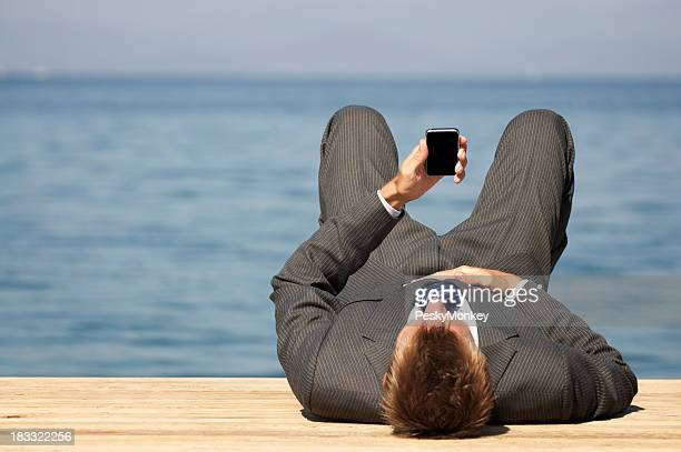 Relaxed Businessman Lying Outdoors on Dock with Mobile Phone