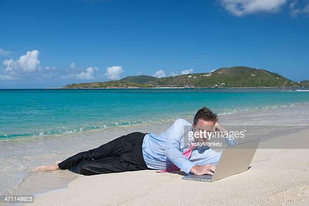 Couché Homme d'affaires décontractée travaillant sur la plage