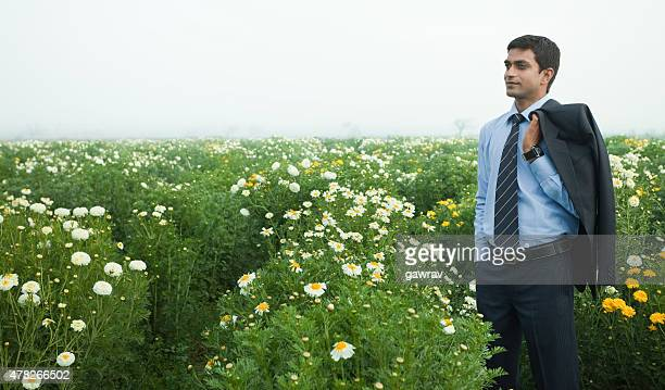 Relaxed businessman standing in lush green field of blossoming marigold.