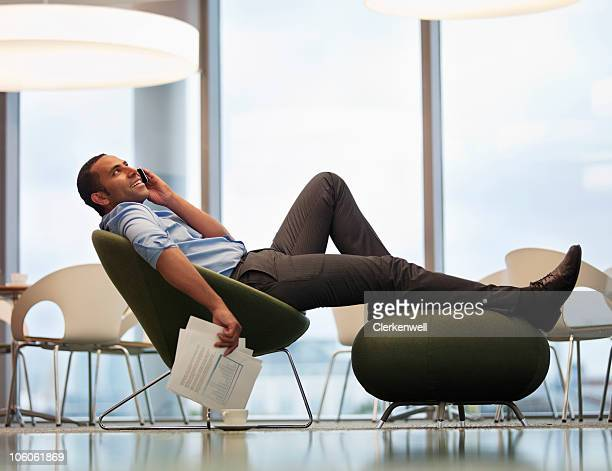 Relaxed businessman using mobile phone at a modern office cafeteria