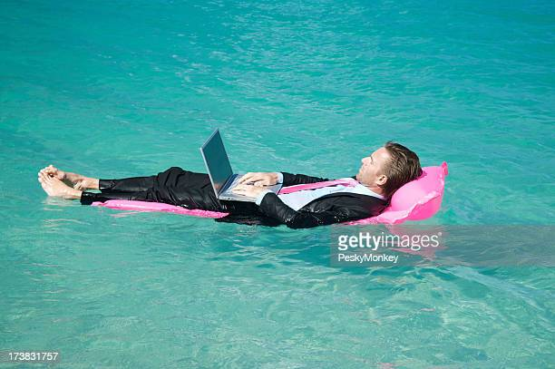 Relaxed Businessman Working Typing on Lilo Floating in Tropical Water