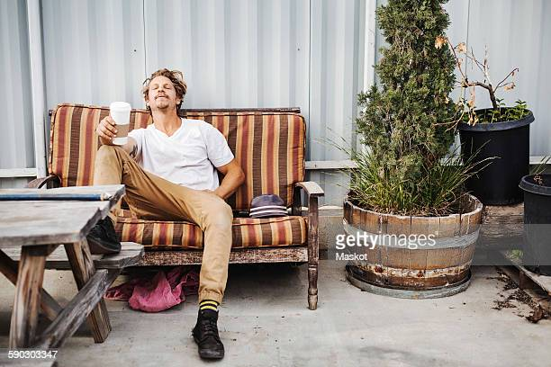 Relaxed carpenter holding disposable cup while sitting on sofa outside workshop