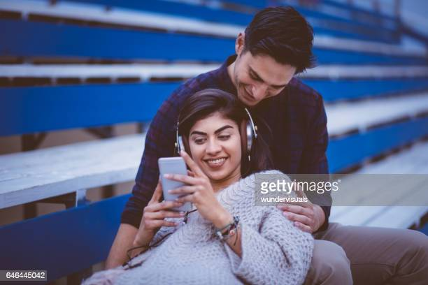 Relaxed couple listening to music on empty stadium stands.