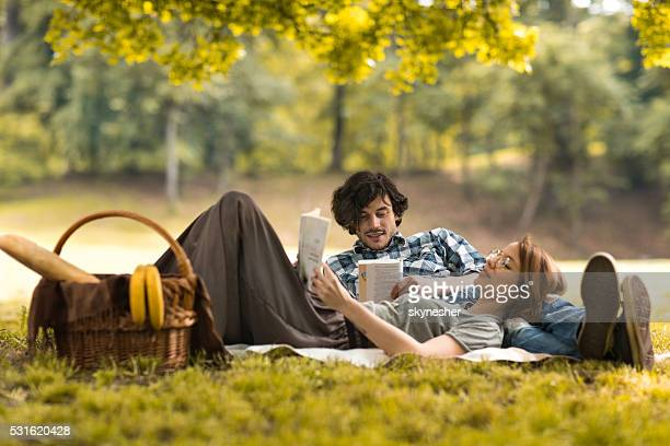 Relaxed couple reading books on picnic during springtime.