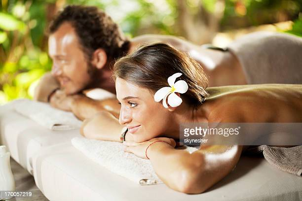 Relaxed couple receiving hot stone therapy.