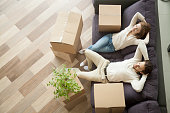 Couple resting on couch after moving in, man and woman relaxing on sofa just moved into apartment with cardboard boxes on floor, happy satisfied homeowners enjoying first day in new home, top view