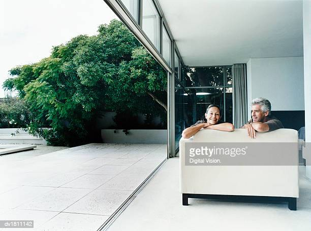Relaxed Couple Sitting on a Sofa in Their Home With French Windows Open Leading to a Garden
