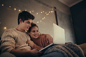 Relaxed young couple sitting on sofa and using laptop at home.  Couple with laptop in cozy living room.