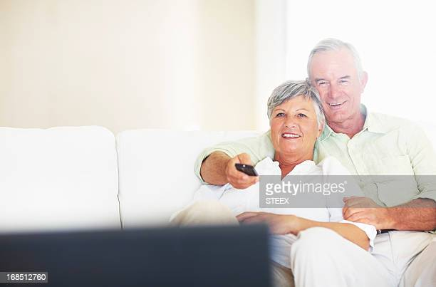 Relaxed couple watching television in living room