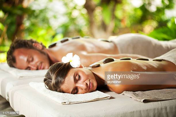 Relaxed couple with eyes closed receiving hot stone therapy