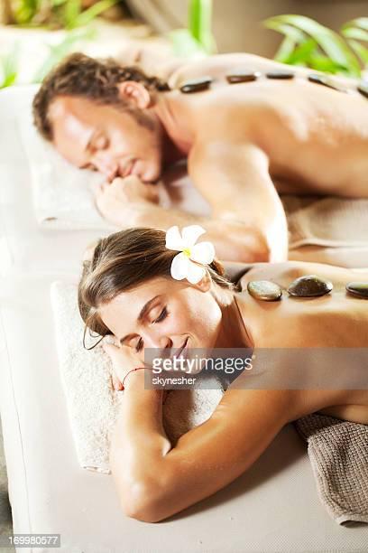 Casal descontraído com olhos fechados com terapia de pedras quente.