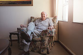 Portrait of a relaxed elderly man sitting on a arm chair at old age home