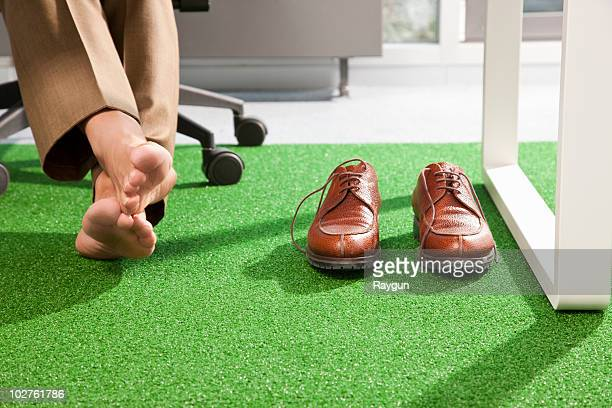 Relaxed feet on a green office carpet