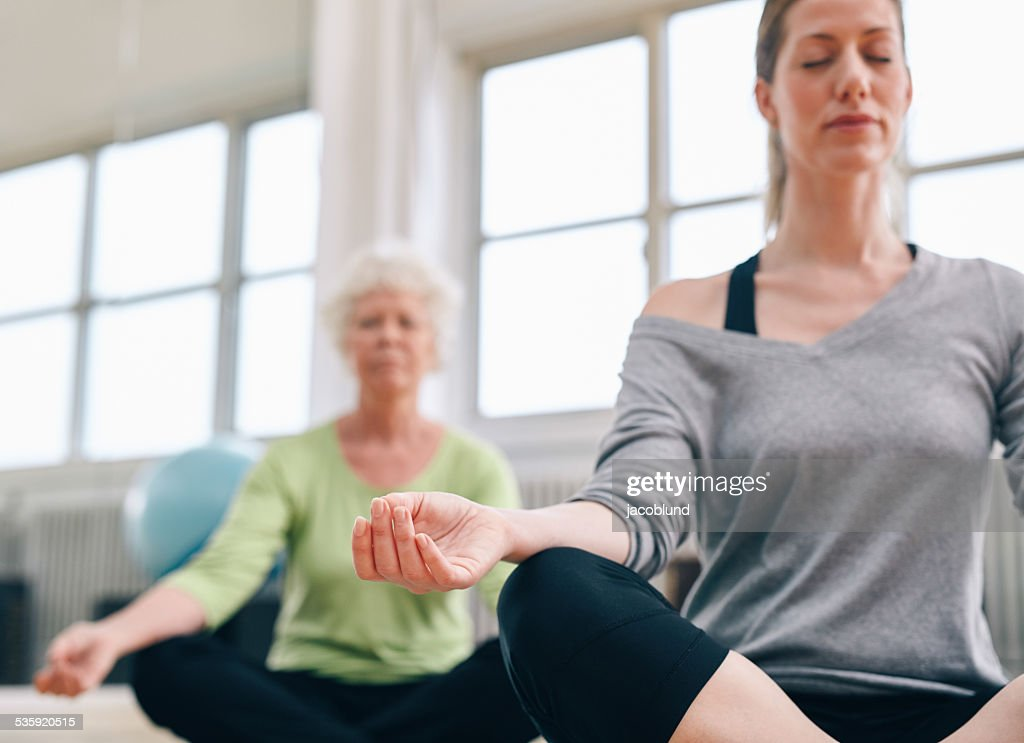 Relaxed fitness women practicing yoga at gym : Stock Photo