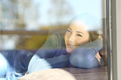 Portrait of a relaxed lady looking through a window lying on a sofa in the living room at home. Outdoor view