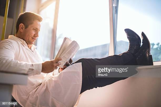 Entspannte männlichen Arzt medizinische Buch lesen am Fenster.