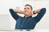 Mature Man Satisfied Sitting In Front Of Laptop Daydreaming